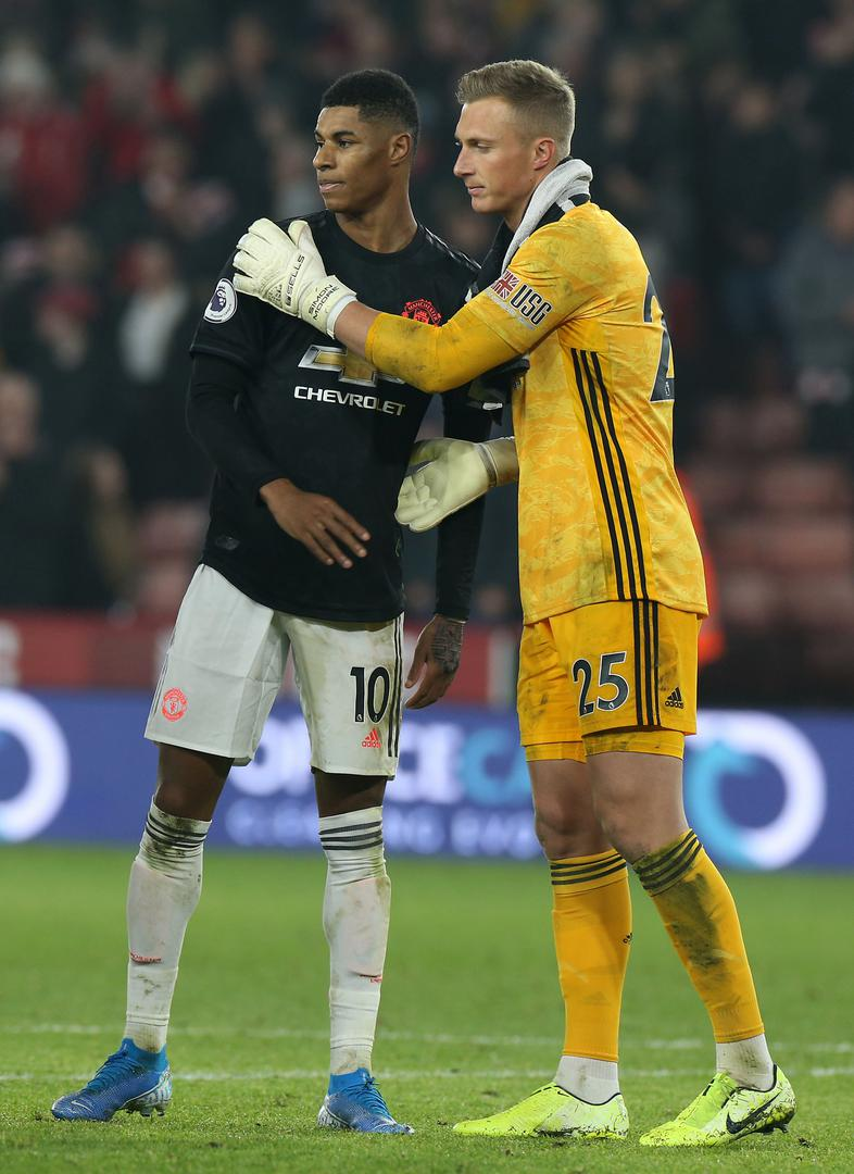 Marcus Rashford shakes hands with Simon Moore