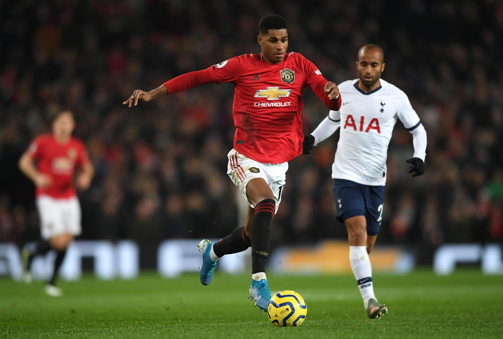 Marcus Rashford races away with 。。the ball, pursued by Lucas Moura