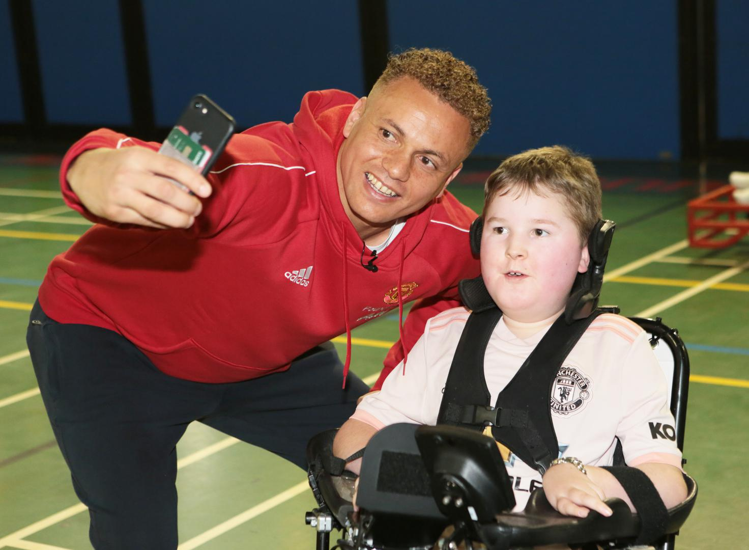 Wes Brown poses for a selfie with a young Manchester United Foundation powerchair player