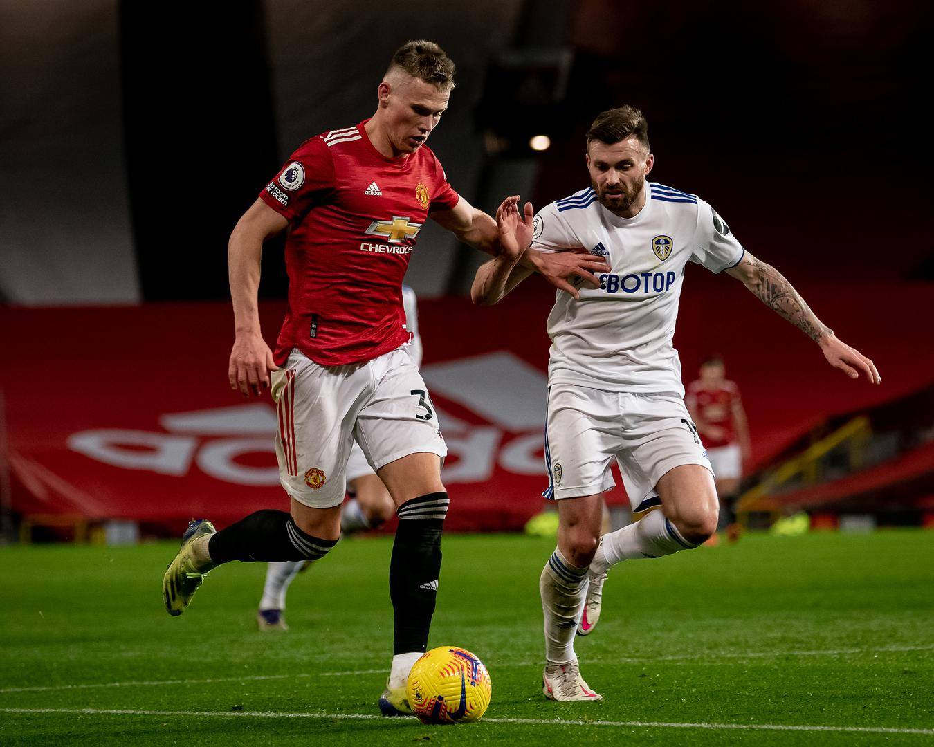 Scott McTominay is challenged by Stuart Dallas