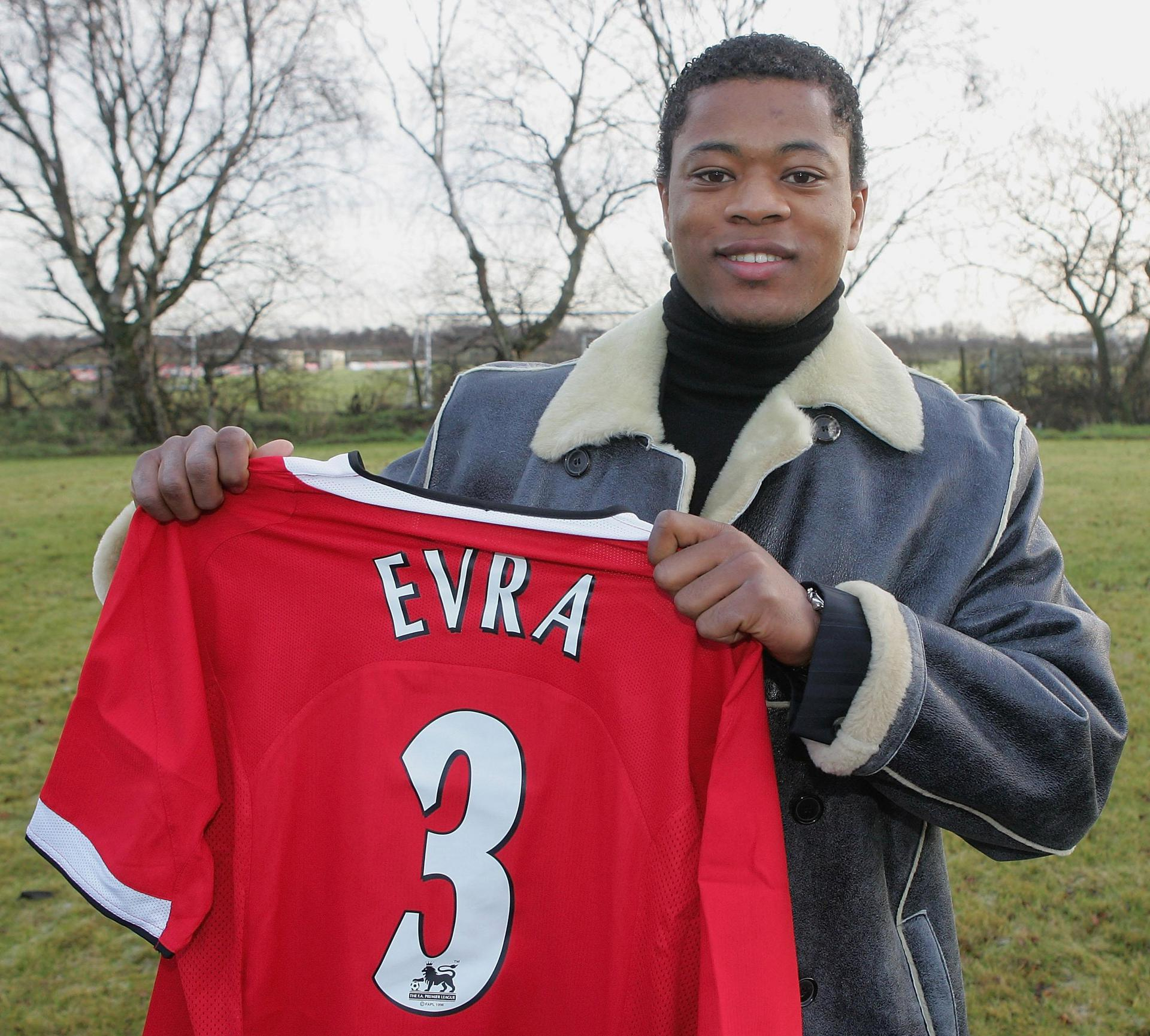 Patrice Evra holds up a United shirt.,